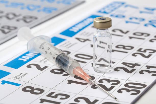 Syringe and Vaccine on a Calendar stock photo
