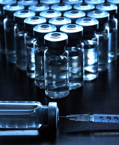 Syringe drawing up medication or drug from medicine bottles stock photo