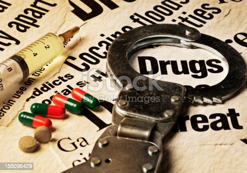 A variety of press cuttings, all dealing with drug abuse, with a worn handcuff circling the word