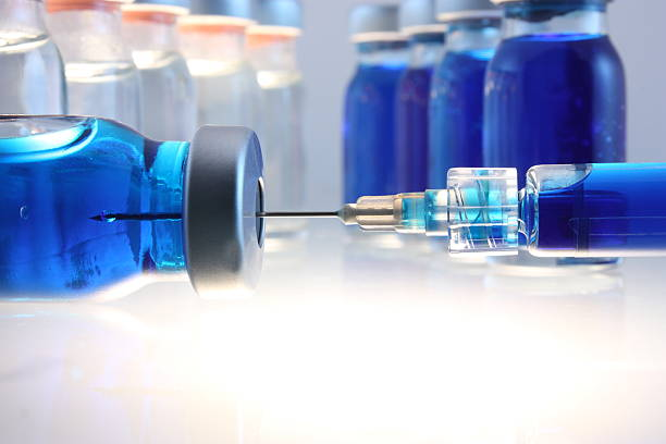 Syringe with blue liquid entering bottle with more behind stock photo