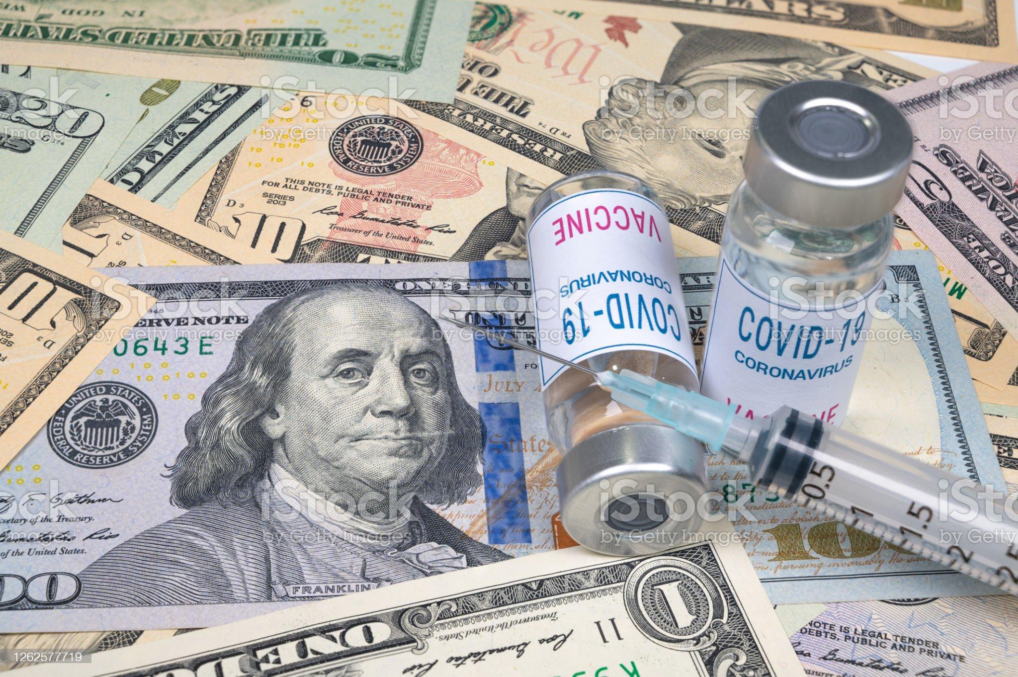 注射器と居心地の良い-19ワクチンアンプルは、米ドルの上に横たわっている。 - ワクチン接種のロイヤリティフリーストックフォト