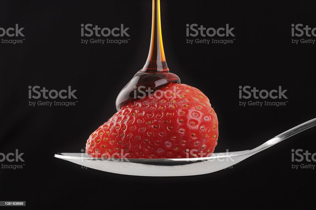 Syrup Being Poured Over Strawberry on a Spoon royalty-free stock photo