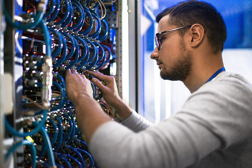 Side  view portrait of young man connecting cables in server cabinet while working with supercomputer in data center