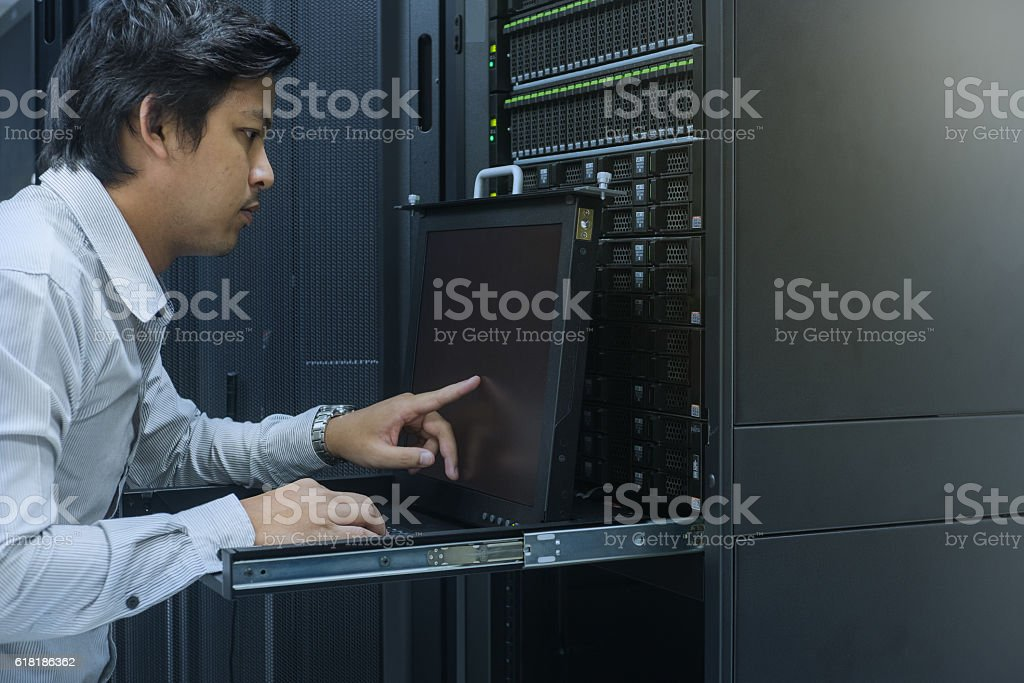 system administrator working in data center stock photo