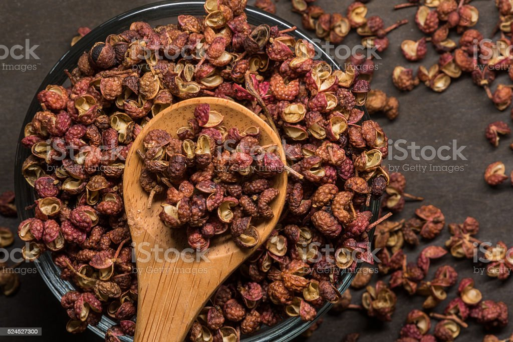 Szechuan Peppercorns in Wooden Spoon With Glass Bowl stock photo