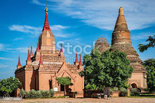 Mee Nyein Gone Phaya Temple with Red Stupas and Ta Wa Gu Pagoda Temple Complex under blue summer sky. The Mee Nyein Gone Temple, built in the 12th century, is south of Bagan City. The name