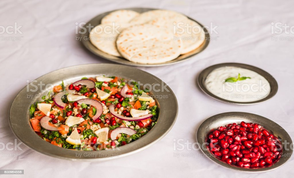 Tabbouleh salad and Arab pita bread with pomegranate seeds and white sour cream sauce against white background. Selective focus. stock photo