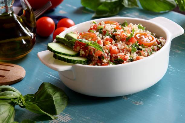 taboulé salat teller auf blauem hintergrund - couscous salat minze stock-fotos und bilder