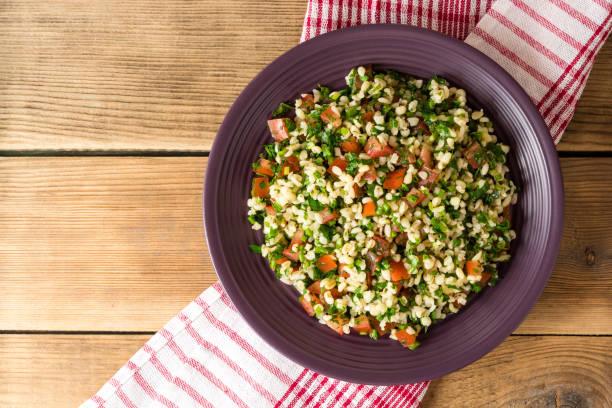 taboulé salat mit bulgur, tomaten, petersilie, frühlingszwiebeln und minze in platte auf holztisch. - couscous salat minze stock-fotos und bilder