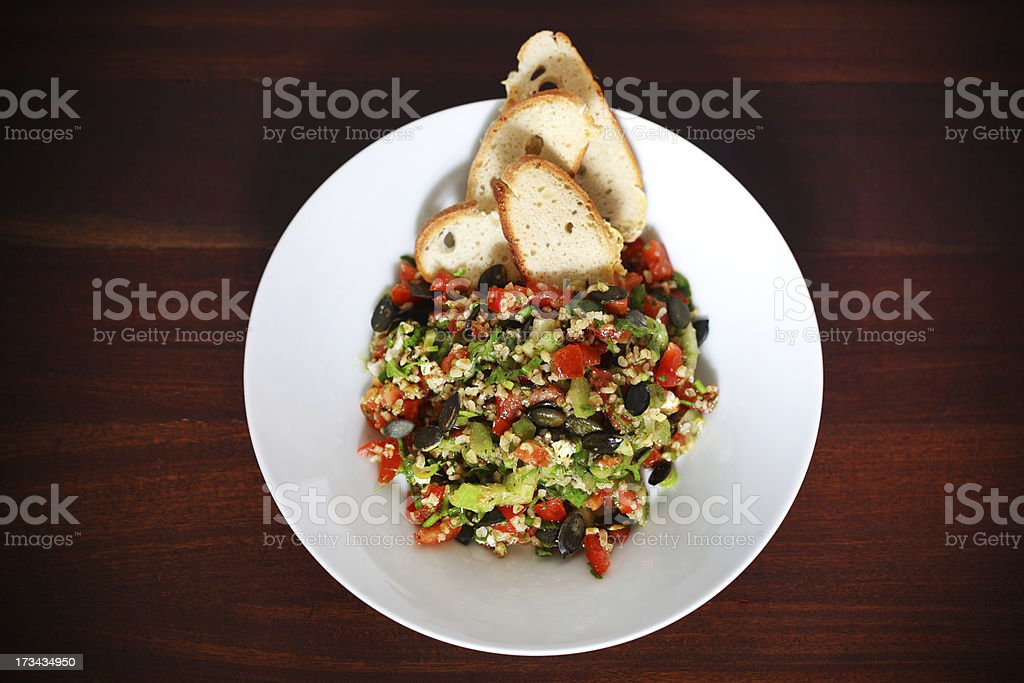 Tabbouleh salad with bulgur wheat, tomatoes, olives and crackers royalty-free stock photo