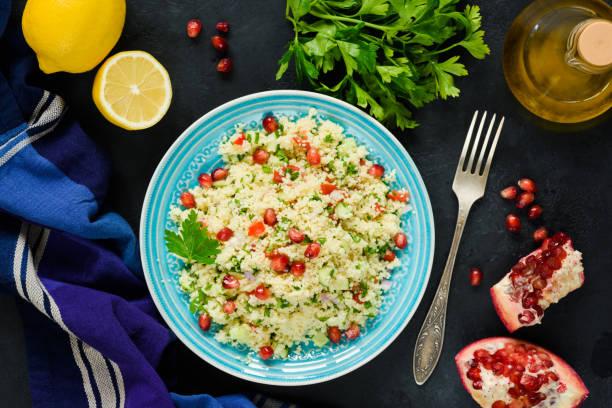 taboulé-salat mit couscous und granatapfel - griechischer couscous salat stock-fotos und bilder