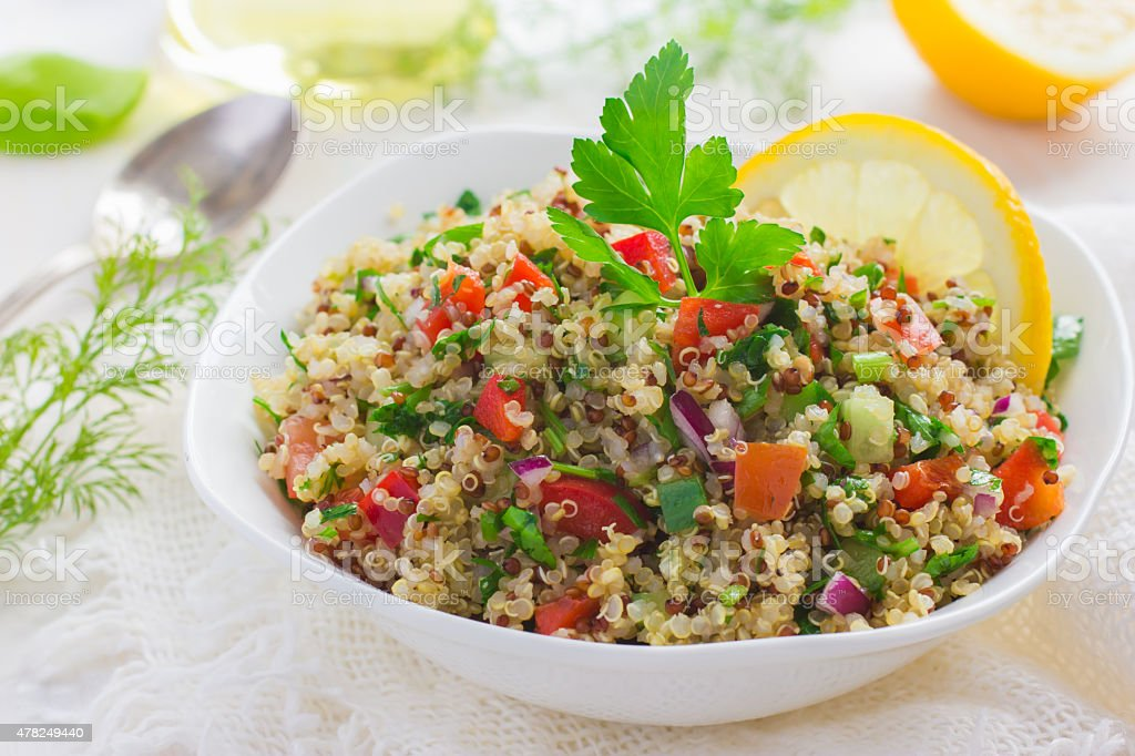 Tabbouleh salad with quinoa, parsley and vegetables Tabbouleh salad with quinoa, parsley and vegetables on white background 2015 Stock Photo
