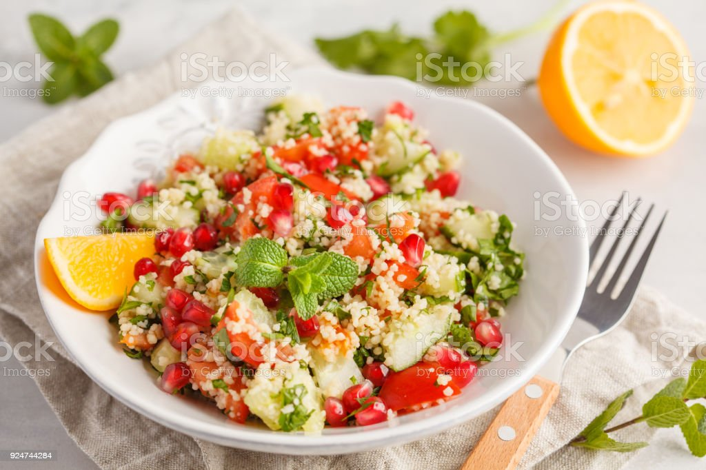 Tabbouleh salad with tomato, cucumber, couscous, mint and pomegranate. Vegan Healthy Food Concept. Traditional middle eastern or arab dish. stock photo
