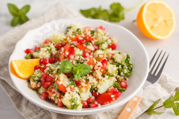 taboulé salat mit tomate, gurke, couscous, minze und granatapfel. vegane ernährung konzept. traditionelle orientalische oder arabische speise. - couscous salat minze stock-fotos und bilder