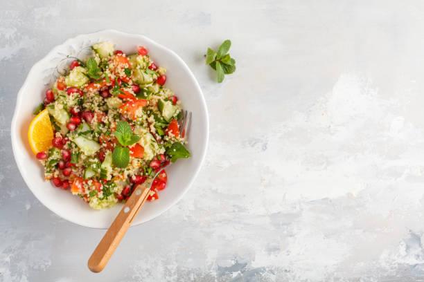 taboulé salat mit tomate, gurke, couscous, minze und granatapfel. ansicht von oben, raum, grauen hintergrund kopieren. vegane ernährung konzept. traditionelle orientalische oder arabische speise. - couscous salat minze stock-fotos und bilder