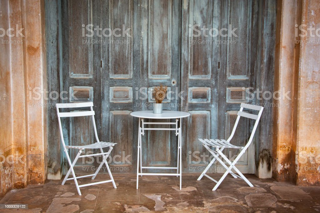 Table and chairs An open terrace in a cafe, shelf in front of wooden door and old house, selective focus, copy space