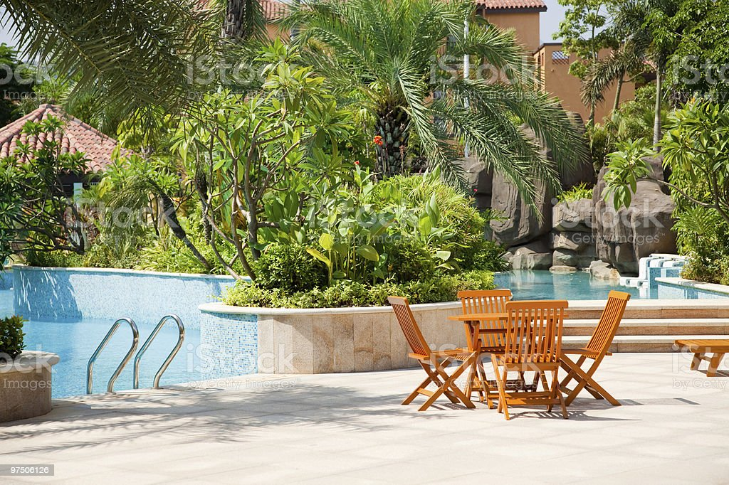 Table and chairs by a swimming pool in the garden royalty-free stock photo