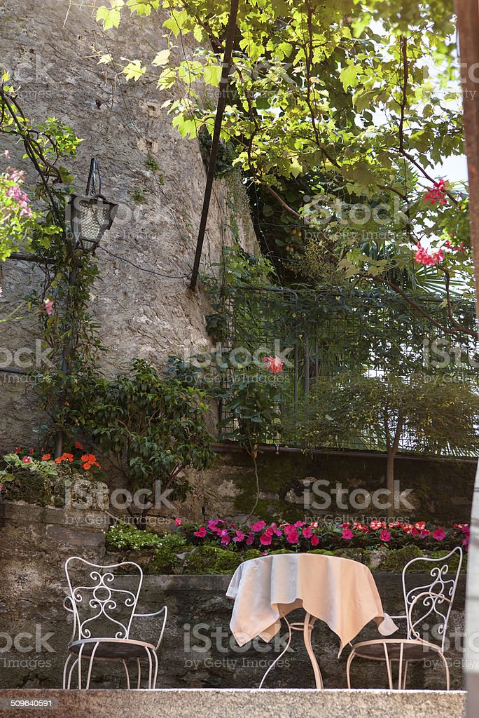 table and chairs in italian garden stock photo