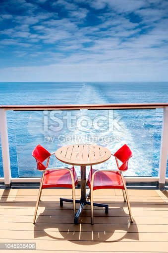 A small round table with two red chairs, on deck at the stern of a cruise ship