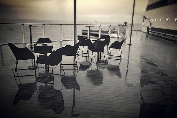Mesa e cadeiras no deque de um navio - foto de acervo