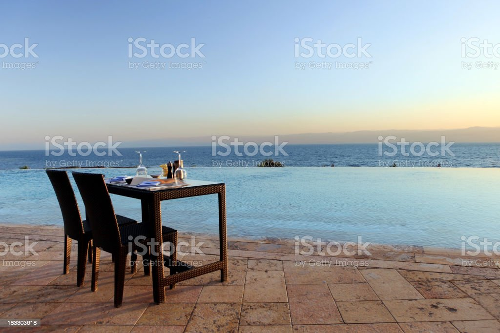 Table and chairs set overlooking the water stock photo
