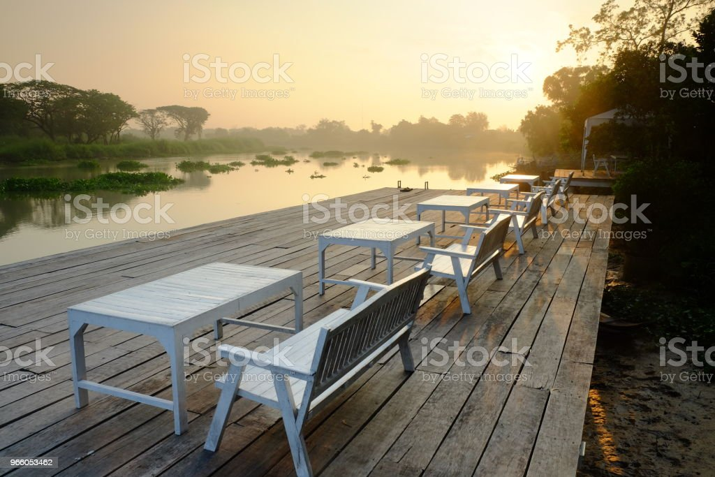 Table and seats on terrace at river side  in the morning , thailand - Royalty-free Beauty Stock Photo