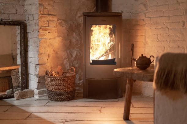table and teapot near wood stove fireplace in comfort house with cozy interior in room. wicker basket with firewood near chimney with metal body and glass door - hygge imagens e fotografias de stock