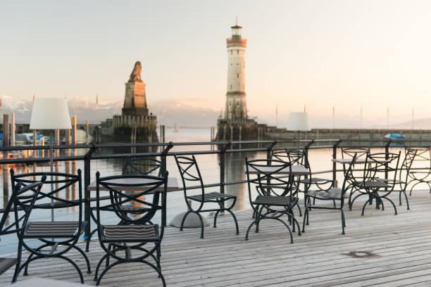 Tisch und zwei Stühle vor der Kulisse Lindauer Hafen Abends am Lindauer Hafen und ein chicer Tisch und zwei 2 Stühle vor der prachtvollen Kulisse des Lindauer Hafens am Bodensee. Die Schärfe liegt auf dem Vordergrund. z_wei stock pictures, royalty-free photos & images