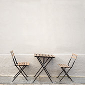 outdoor table and two chairs near the wall at coffee shop, Bergen, Norway
