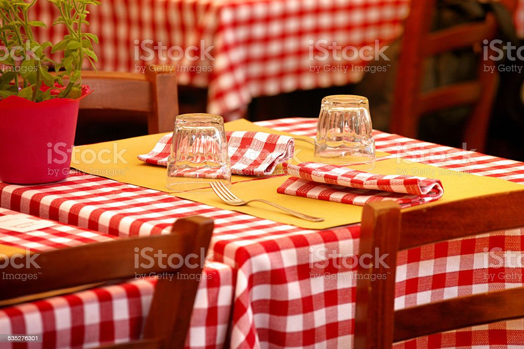 Table setting with dishware and glasses at italian restaurant, with...