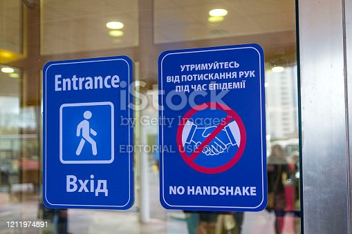 Kiev, Ukraine - March 11, 2020: Table at the entrance to the office building to renounce greetings handshake during an epidemic in the English and Ukrainian languages