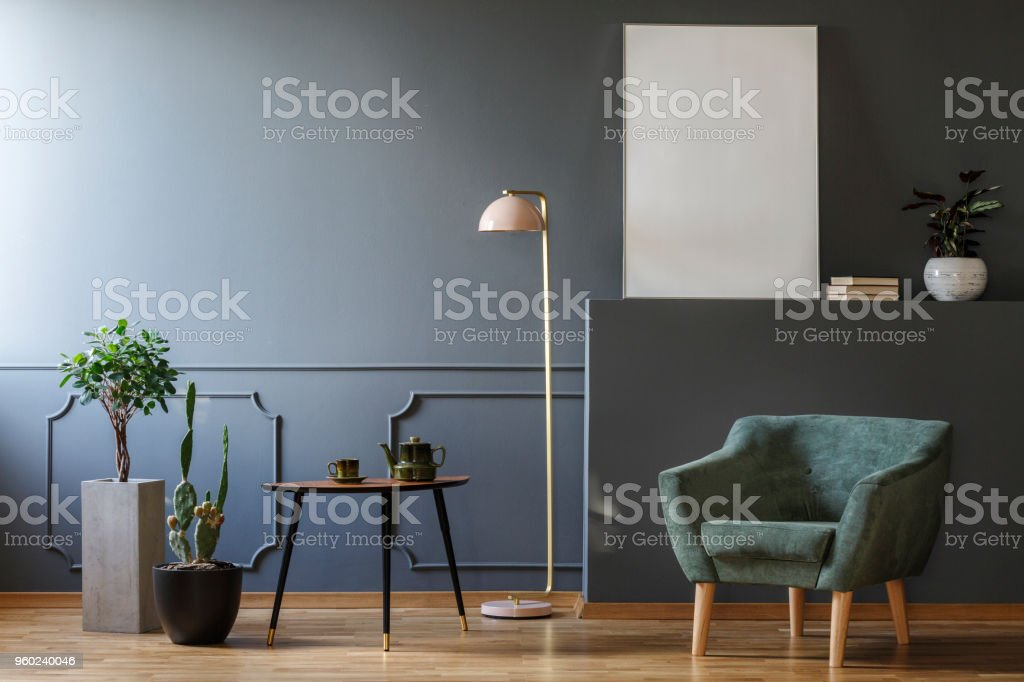 Table between plants and lamp in grey apartment interior with green armchair and mockup stock photo