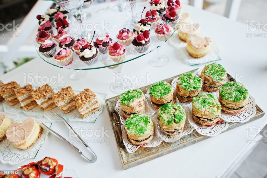 Table Catering With Different Cakes And Cupcakes At Wedding