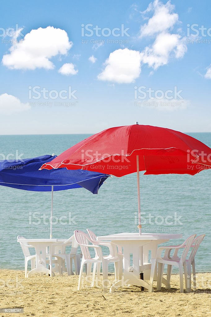Table, chairs and parasol on  the beach royalty-free stock photo