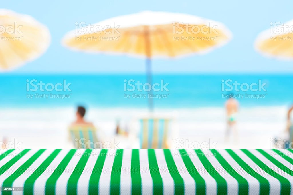 Table Covered With Green Striped Tablecloth On Blurred Beach Background  Royalty Free Stock Photo