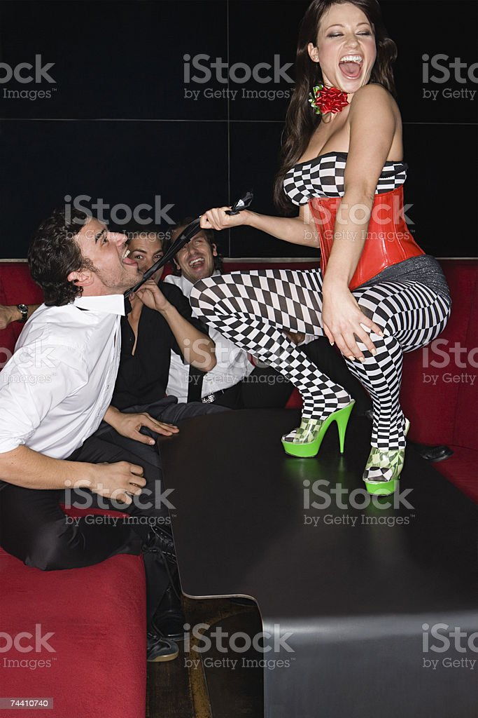 Table dancer pulling mans tie stock photo