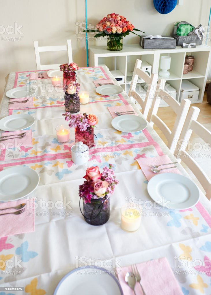 Table decoration for bithday party with flowers, candles und dishes stock photo