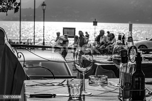 Tourist pass by an empy table for two on the shore line of Varenna on Lake Como Italy.
