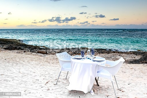 Table for two on the beach at sunset. Romantic dinner