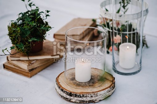 istock Table for wedding ceremony is decorated with flowers, cage, candles, books and greens, greenery. Compositions of wedding wooden decor in the backyard banquet area. Close up. Artwork in style vintage. 1132126410