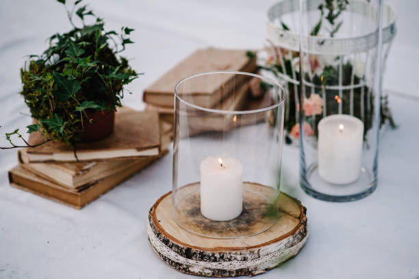 table for wedding ceremony is decorated with flowers, cage, candles, books and greens, greenery. compositions of wedding wooden decor in the backyard banquet area. close up. artwork in style vintage. - home decor boho imagens e fotografias de stock