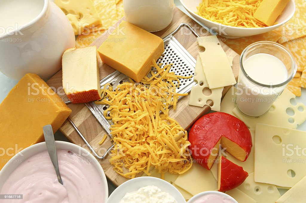 A table full of yogurt, milk, and assorted cheeses stock photo