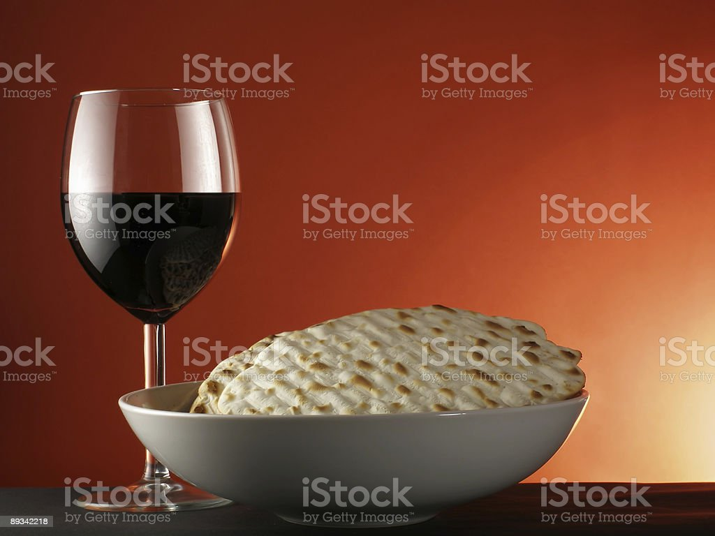 A table holding a glass of wine and a bowl of matzoh royalty-free stock photo
