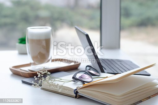 istock A table in a bright cafe with latte and freelancer work details. 1129330821