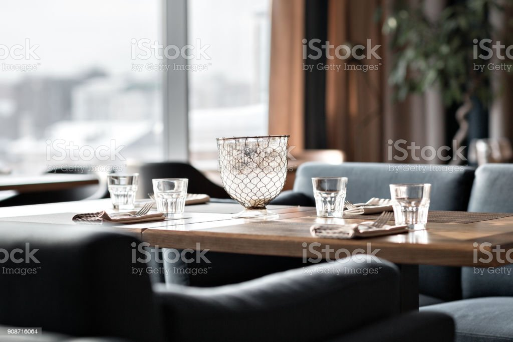 Table in restaurant served for lunch. Glasses, flower fork, knife served for dinner in restaurant with cozy interior stock photo