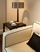 an elegant lamp with shade on a coffee side table next to a cream coloured settee. Set in a luxury apartment show home and furnished by an interior designer. Two cups with saucers are carefully composed next to the lamp on the table. A shadow of the lamp shades on the wall (caused by the downlighting) adds nicely to the overall composition.Looking for a Living Room image Then please see my other Living Room and related images by clicking on the Lightbox link below...