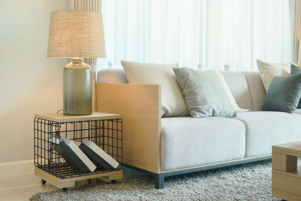 Table lamp next to comfy sofa in modern style living room - foto stock