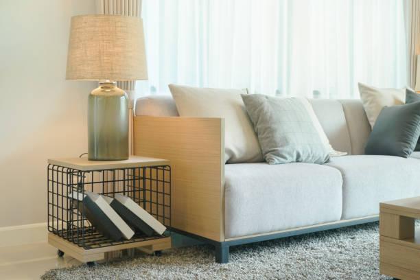 tischleuchte neben bequemen sofa im wohnzimmer im modernen stil - tischsofa stock-fotos und bilder