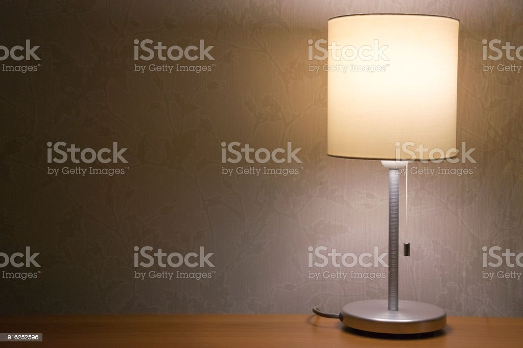 Table lamp over white wall background. Modern minimalistic night...