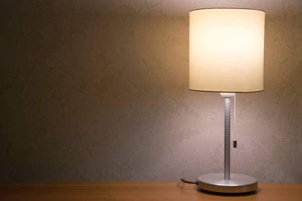 Table lamp over white wall background. Modern minimalistic night light for bedroom interior stock photo